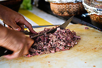 Detail of chef's hands as he chops meat with knife on a white cutting board in a street cafe, San Felipe, Baja California, Mexico