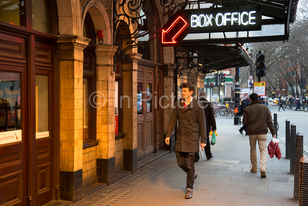 Man walking past the box office for the Palace Theatre in the West End of London, UK. This area, known for it's many theatres and playhouses, is known as Theatreland.