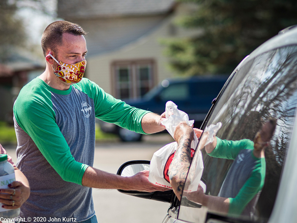 """26 APRIL 2020 - JEWELL, IOWA: GARREN ZANKER, hands a bag of """"grab and go"""" roast pork dinners to a motorist in Jewell during a fund raiser Sunday. Jewell, a small community in central Iowa, became a food desert when the only grocery store in town closed in 2019. It served four communities within a 20 mile radius of Jewell. Some of the town's residents are trying to reopen the store, they are selling shares to form a co-op, and they hold regular fund raisers. Sunday, they served 550 """"grab and go"""" pork roast dinners. They charged a free will donation for the dinners. Despite the state wide restriction on large gatherings because of the COVID-19 pandemic, the event drew hundreds of people, who stayed in their cars while volunteers wearing masks collected money and brought food out to them. Organizers say they've raised about $180,000 of their $225,000 goal and they hope to open the new grocery store before summer.            PHOTO BY JACK KURTZ"""