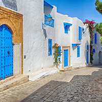 idi Bou Said. Tunisia. View of typical quite peaceful cobbled alleyway lined with whitewashed walls and blue doors and blue window grills in the cliff top village of Sidi Bou Said.