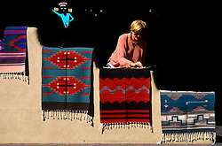 Woman Looking at Rugs Made by Native American Indians