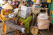 """12 APRIL 2012 - HO CHI MINH CITY, VIETNAM: Vendors read a newspaper in a neighborhood in Binh Tay Market. The market is warren of narrow halls and alleys and steep staircases and still relies on manual labor to move goods. Binh Tay market is the largest market in Ho Chi Minh City and is the central market of Cholon. Cholon is the Chinese-influenced section of Ho Chi Minh City (former Saigon). It is the largest """"Chinatown"""" in Vietnam. Cholon consists of the western half of District 5 as well as several adjoining neighborhoods in District 6. The Vietnamese name Cholon literally means """"big"""" (lon) """"market"""" (cho). Incorporated in 1879 as a city 11km from central Saigon. By the 1930s, it had expanded to the city limit of Saigon. On April 27, 1931, French colonial authorities merged the two cities to form Saigon-Cholon. In 1956, """"Cholon"""" was dropped from the name and the city became known as Saigon. During the Vietnam War (called the American War by the Vietnamese), soldiers and deserters from the United States Army maintained a thriving black market in Cholon, trading in various American and especially U.S Army-issue items.             PHOTO BY JACK KURTZ"""