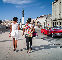 Old Havana, Cuba. Havana vieja, street. Two women walking, vinatage car, transport.