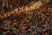Hindu devotees throw coloured powder inside a temple during Holi, the Festival of Colours, Radha Rani Temple, Barsana, India