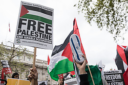 London, UK. 11th May, 2021. A man holds up a Free Palestine placard and a training shoe on which an Israeli flag has been painted on the sole as thousands of people attend an emergency protest in solidarity with the Palestinian people organised outside Downing Street by Palestine Solidarity Campaign, Friends of Al Aqsa, Stop The War Coalition and Palestinian Forum in Britain. The rally took place in protest against Israeli air raids on Gaza, the deployment of Israeli forces against worshippers at the Al-Aqsa mosque during Ramadan and attempts to forcibly displace Palestinian families from the Sheikh Jarrah neighbourhood of East Jerusalem.