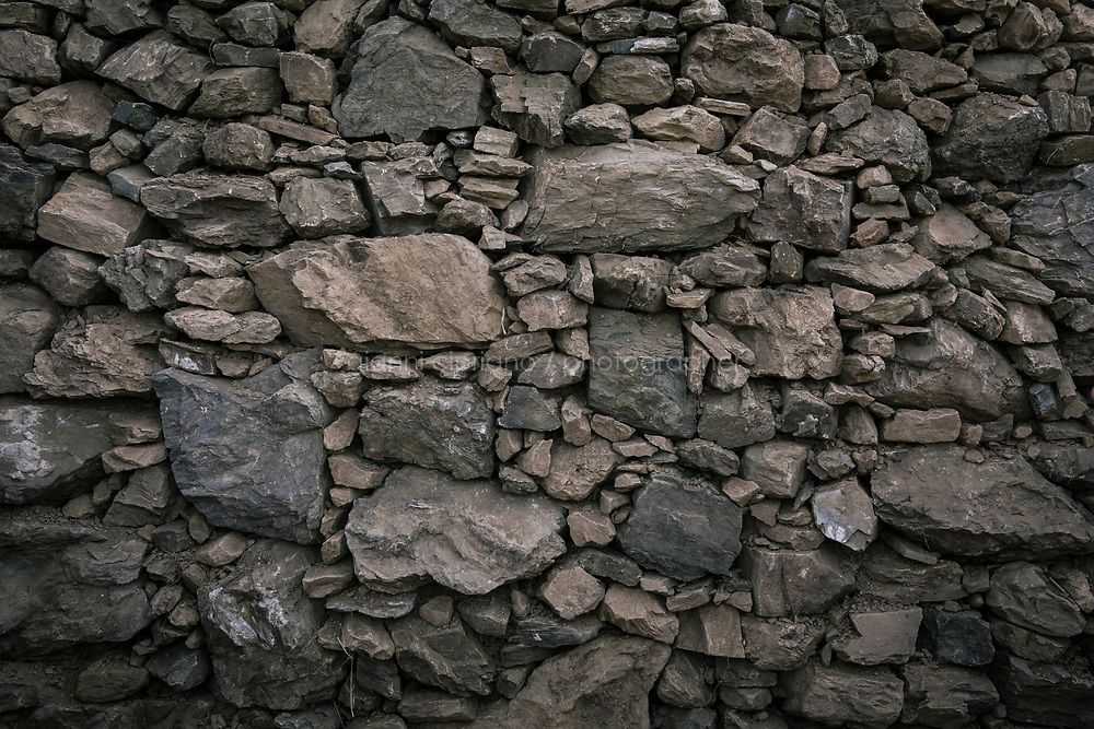 VERNAZZA, ITALY - 1 JUNE 2017: A dry stone wall restored by Margherita Ermirio, a 32 years old local who has spent years abroad and is now the pillar of the battle to restore dry stone walls and preserve the terracing, is seen in Vernazza, Italy, on June 1st 2017.<br /> <br /> She wants to show younger generations the backbone of the Cinque Terre landscape, and teach them why it's crucial to maintain their dry stone walls, dovetailed to hold the soil behind and above.<br /> <br /> Given its jagged coastline and manifold mountainous chains, Italy is believed to hold a record in Europe with an estimated 300,000 hectares of terracing, and 170,000 kilometers of dry stone walls— 20 times the length of the Great Wall of China.<br /> Liguria, the narrow half-moon shaped region along the northern<br /> Thyrrenian sea, has the highest concentration, and terracing is in<br /> poor shape there. In Vernazza, almost half of the terracing is in<br /> ruins.<br /> <br /> Terraced vineyards, apple and lemon groves horizontally run around the green slopes of the Cinque Terre. The stone walls have allowed such vital cultivation in the area and prevented land slides. Since the 1960s, the ancient walls have been largely<br /> abandoned, posing hydro-geological threats to the same villages during<br /> heavy rains and, in general, as time passes.<br /> <br /> Since the 2012 flood - when tons of mud invaded the<br /> village's main road, shops and and homes, isolating the area and<br /> taking three lives - Margherita Ermirio has agreed with the various land lords to take<br /> over 6,000 square meters of land parcels that needed to be cleaned up,<br /> in order to fix them and thus prevent land slides, but also to show to<br /> the younger generations that agriculture is still possible in the<br /> Cinque Terre.