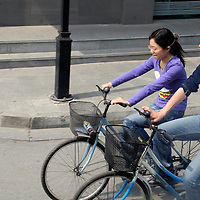 Asia, China, Beijing. Young couple riding bikes on streets of Beijing.