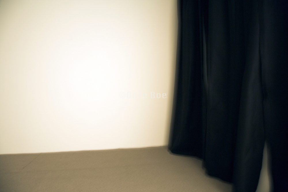 detail of a black curtain against a white wall camera motion blurred