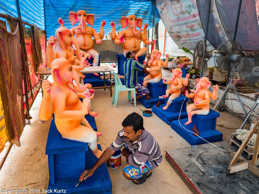 """29 AUGUST 2016 - BANGKOK, THAILAND: Craftsmen at the Vishnu Temple in Bangkok paint a statue of Ganesha, an important Hindu deity known as the """"overcomer of obstacles."""" Ganesha Chaturthi is the Hindu festival celebrated on the day of the re-birth of Lord Ganesha, the son of Shiva and Parvati. Ganesha is widely revered as the patron of arts and sciences and the deva of intellect and wisdom. The last day of the festival is marked by the immersion of the deity in nearby bodies of water. The immersion symbolizes the cycle of creation and dissolution in nature. The deities made at the Vishnu Temple in Bangkok will be submerged in rivers and streams across Thailand at several Ganesha festivals held in September.          PHOTO BY JACK KURTZ"""