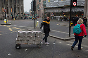 An Evening Standard newspaper vendor pulls a trolley of copies over Bank Triangle junction, in the Square Mile, the capitals oldest district and financial centre, on 9th February 2017, in the City of London, England.