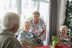 Senior man and women with rose flower at rest home, Bavaria, Germany, Europe