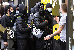 © Licensed to London News Pictures. 02/12/2020. London, UK. A worker speaks to shoppers as they queue outside a branch of JD Sports on Oxford Street. Today England returns to tiered COVID restrictions following the end of the second national lockdown. Photo credit: George Cracknell Wright/LNP