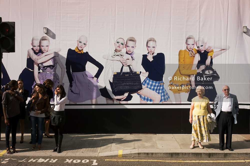 Young women on a shop hoarding with pedestrians and an elderly couple about to cross Brutoin Street.