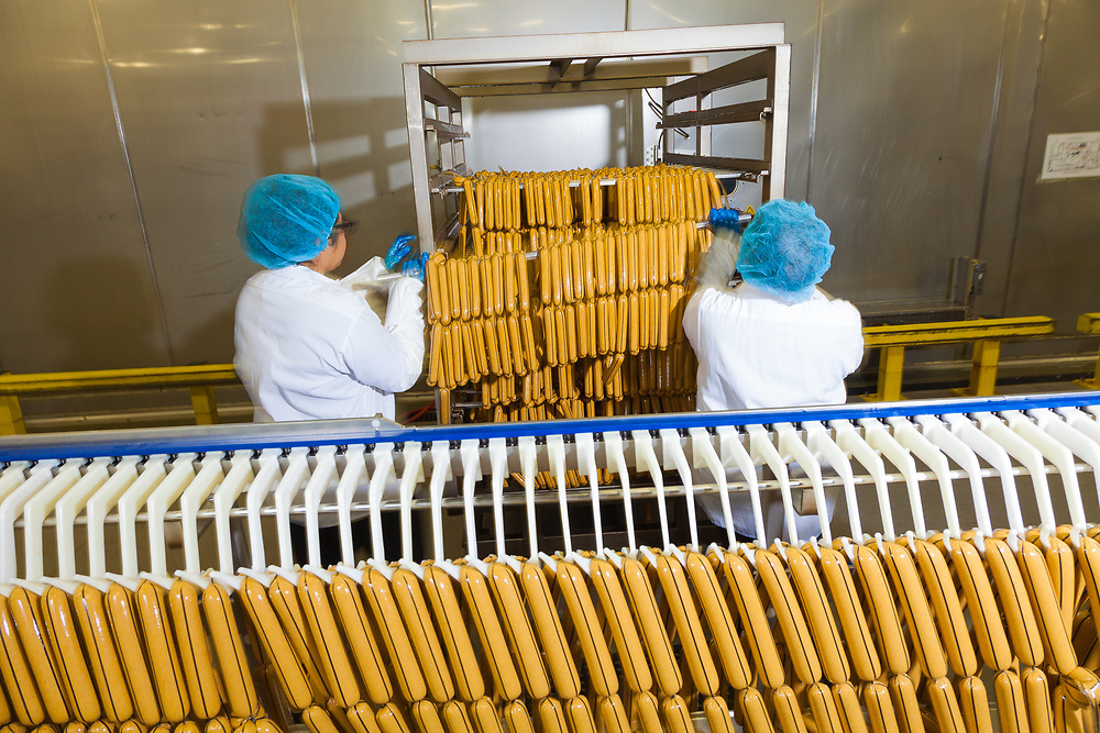 Cased sausages loaded onto racks before being sent to the ovens for baking and smoking. Sausage processing at Tofurky processing facility  in Hood River, Oregon