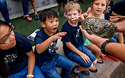 Tony Nguyen, 7, second from left, reacts as he checks out an African bull frog during a reptile show at Iglesia Park Community Center in Aliso Viejo, CA. Kids were treated to the show by the Reptile Zoo of Fountain Valley, CA.