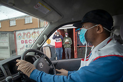 """Eugene Hadley, of African Jam, delivers bread to the community of Parkwood, a subburb of Cape Town, located on the Cape Flats, Monday, April 20, 2020. The majority of the people who live here are unemployed during """"normal"""" circumstances. And as South Africa is now in lockdown due to the Coronavirus, many of those who had jobs have also lost their income. So many people are starving. The feeding scheme is a joint community effort, paid for solely by donations from the public to feed more than 3,000 households. The group is also receiving transportation support by The South African Red Cross Society. PHOTO: EVA-LOTTA JANSSON"""