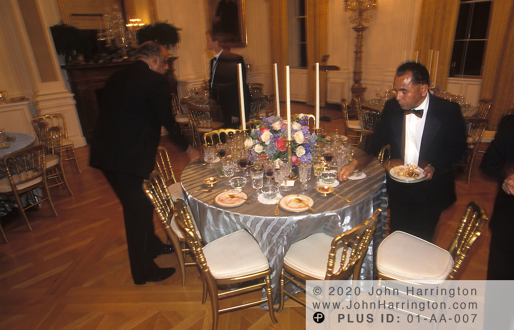 AS GUESTS DANCE THE NIGHT AWAY, THE BUTLERS QUIETLY REMOVE THE SETTINGS FROM THE TABLE AFTER AN ENJOYABLE STATE DINNER.