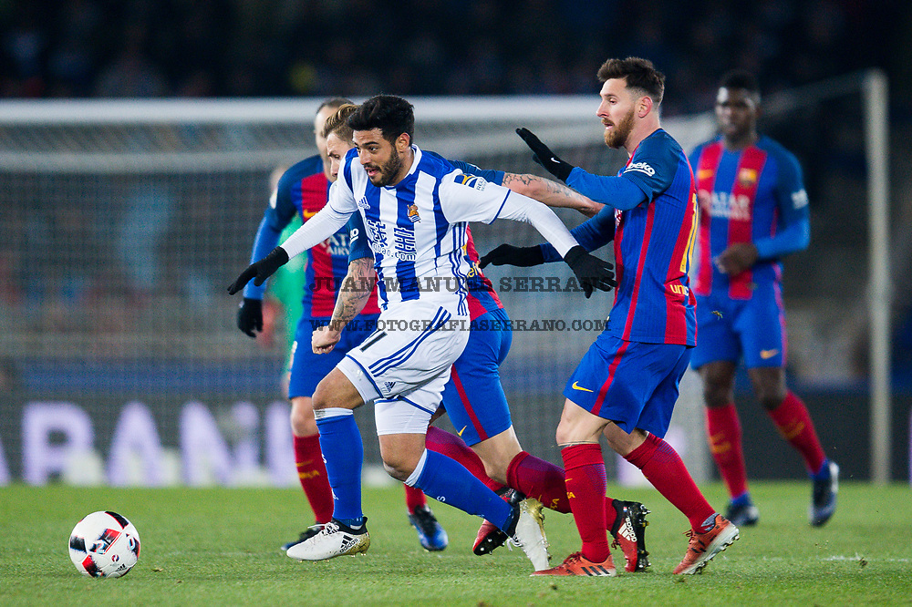 SAN SEBASTIAN, SPAIN - JANUARY 19:  Carlos Vela of Real Sociedad duels for the ball with Lucas Digne and Lionel Messi of FC Barcelona during the Copa del Rey Quarter Final, First Leg match between Real Sociedad de Futbol and FC Barcelona at Estadio Anoeta on January 19, 2017 in San Sebastian, Spain.  (Photo by Juan Manuel Serrano Arce/Getty Images)