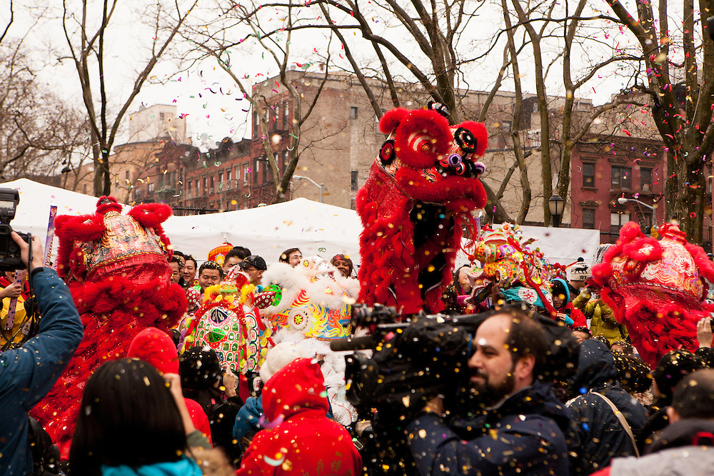 Confetti from party poppers fills the air around the dancing dragons.