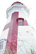 A low angled viewpoint of the East Quoddy Lighthouse, with high contrast and sun flare.