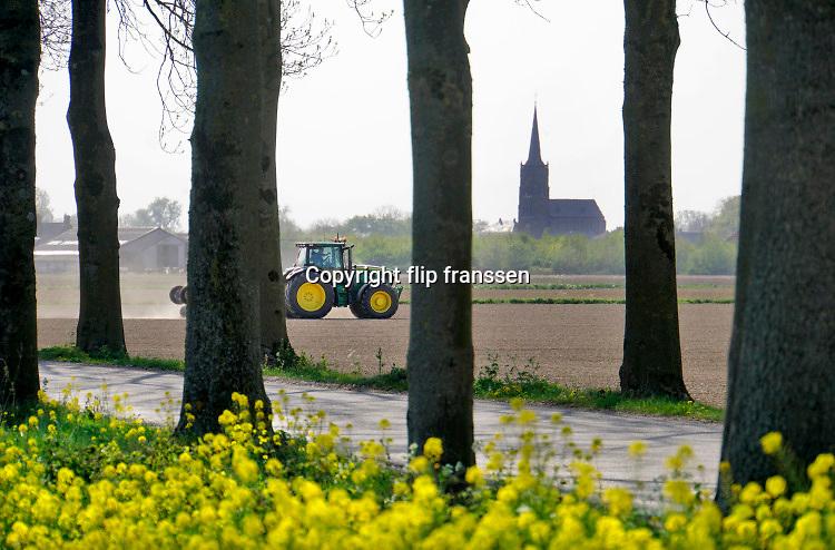 Nederland, Batenburg, 17-4-2020 Een boer, loonwerker, egaliseert de grond via een mechaniek achter de tractor.  De grond is droog door het drie weken uitblijven van regen.Foto: Flip Franssen