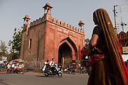 An Indian woman dressed in a red sari is passing by the Taj Gate, another monument of great Mughal architecture in Agra.
