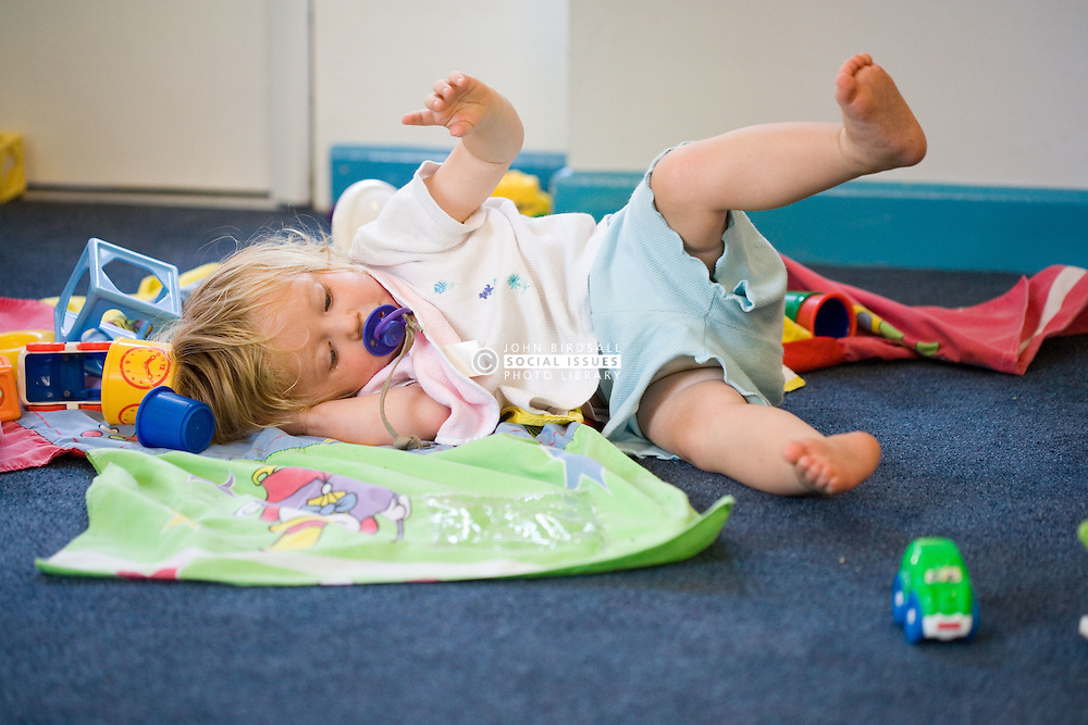 Baby at Nursery School; rolling around on the floor,