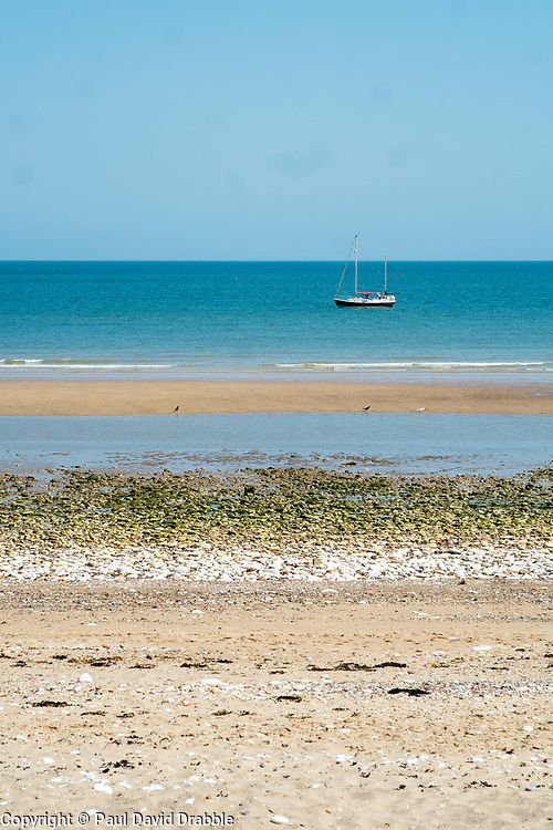 Bridlington North Beach with a small Yacht sitting out in the bay<br /> <br />   05 July 2018 <br />   Copyright Paul David Drabble<br />   www.pauldaviddrabble.co.uk