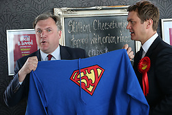 "© Licensed to London News Pictures . 11/04/2015 . Bury , UK . Labour Shadow Chancellor Ed Balls (l) and James Frith (c) , Labour candidate for Bury North , at a campaign stop at Barista coffee shop at The Rock , Bury in Greater Manchester , UK . Pictured holding a "" Super Josh "" brain tumour charity sweatshirt . The pair met parents and discussed family finances . Photo credit : Joel Goodman/LNP"