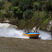 A jet boat from Bridge to Nowhere tours heads along the Whananui River in the Whanganui National Park..The park encloses the wild upper and middle reaches of the Whanganui River, which is New Zealand's longest navigable waterway. Beginning beneath the shadow of the central plateau's giant volcanoes, the 329 kilometre river winds its way to the Tasman Sea through an endless procession of forested valleys and hills. 30th December 2010. Photo Tim Clayton.