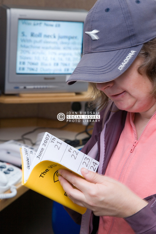 Woman looking at a large print diary suitable for sight impaired people,