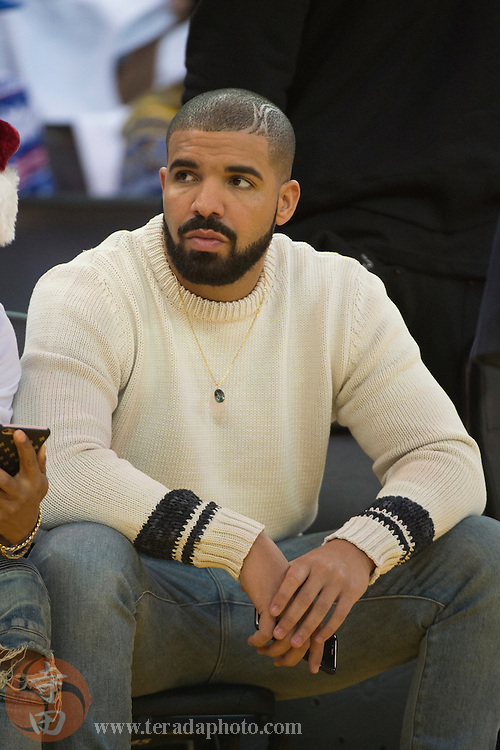 December 25, 2015; Oakland, CA, USA; Recording artist Drake sits courtside before a NBA basketball game on Christmas between the Golden State Warriors and the Cleveland Cavaliers at Oracle Arena. The Warriors defeated the Cavaliers 89-83.