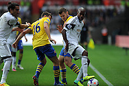 Swansea city's Dwight Tiendalli holds off Arsenal's Aaron Ramsey (16) and Jack Wilshere. Barclays Premier league, Swansea city v Arsenal at the Liberty Stadium in Swansea on Saturday 28th Sept 2013.  pic by Andrew Orchard, Andrew Orchard sports photography.