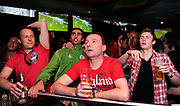 England football fans watch England play football on television in a bar in central London.