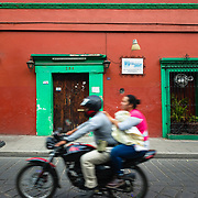 Motorbike passing a Spanish Colonial building in Oaxaca, Mexico