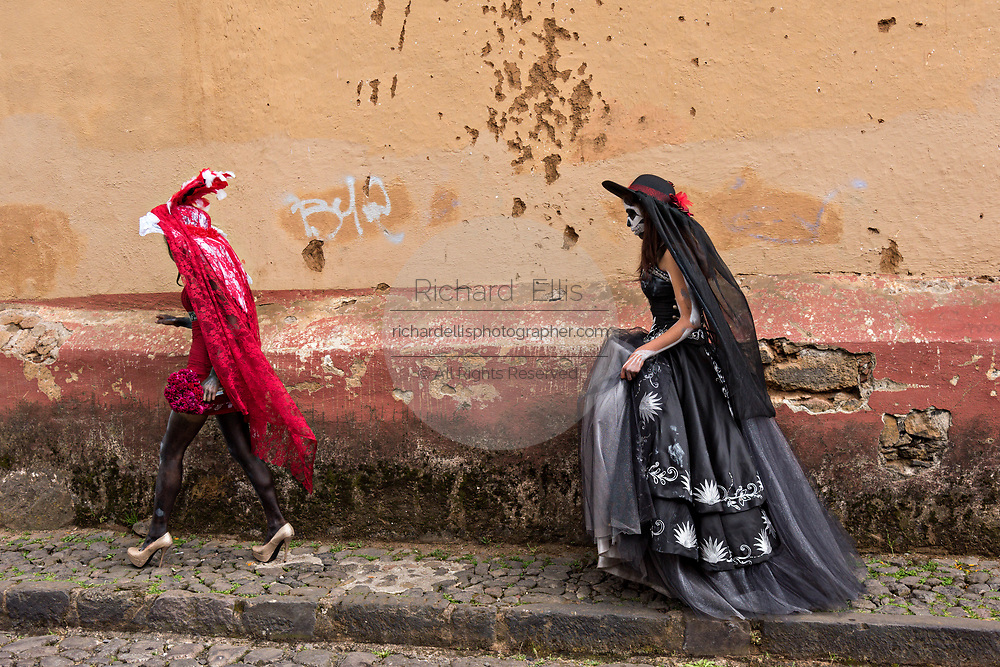 Young Mexican women dressed in La Calavera Catrina costumes walk along a wall during the Day of the Dead or Día de Muertos festival October 31, 2017 in Patzcuaro, Michoacan, Mexico. The festival has been celebrated since the Aztec empire celebrates ancestors and deceased loved ones.