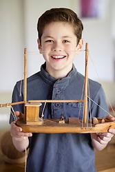 Boy Holding Model Ship