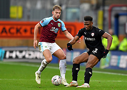 Burnley's Charlie Taylor (left) and Barnsley's Dimitri Cavare (right) battle for the ball during the Emirates FA Cup, third round match at Turf Moor, Burnley.