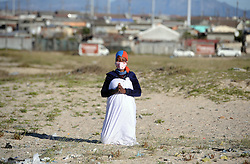 South Africa - Cape Town - 2020-05-06 S Nomatter Nhaka 40 year old from Zimbabwe praying for Coronavirus and her Situation, She praying at the field that they use as church (John Masowe Nyenyendzi Nonki) in Kuyasa Khayelitsha. South Africa  embark on a staged reopening of the economy, started with a level 4 on the first of May, to help slow down the spread of coronavirus, and ensure that health authorities are not overwhelmed, you can not attend church or other public gatherings Photographer Ayanda Ndamane African news