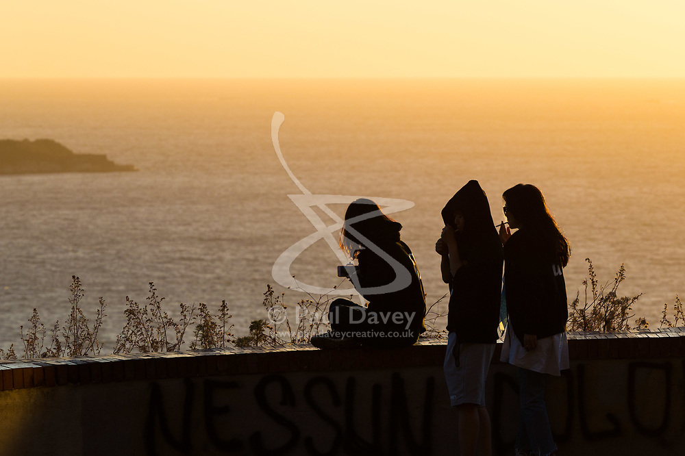 Sorrento, Italy, September 17 2017. Friends admire the sunset from a vantage point on the road above Sorrento, Italy. © Paul Davey