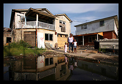 19 August 2006 - New Orleans - Louisiana. Faith Figueroa. Finding Faith. Faith (2 yrs) with her mother Miriam and her sister Anfernya (5yrs) back in the 9th Ward from which they were evacuated by boat as hurricane Katrina flooded their neighbourhood almost a year ago. The neighbourhood remains desolate, with few residents. Hurricane damage for the most part unrepaired. They now have to share their home with rats. Electricity is sporadic and expensive, the telephone company has still not repaired the lines and someone tried to break into their home a few days ago whilst they were in it. Miriam stands with her children, their home in an upstairs apartment behind them. They escaped into a boat from the top steps as hurricane Katrina flooded the area. A large puddle now forms in the ruined streets, a breeding ground for ferocious mosquitos.