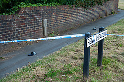 © Licensed to London News Pictures. 27/07/2021. Stoke Poges, UK. A pair of sandals inside a polcie cordon on Bells Hill at the corner of Penn Meadow in Stoke Poges, Buckinghamshire, following an assault on Monday 26 July at approximately 21:30BST. A man in his twenties suffered a serious leg injury following the assault which is understood to have involved a machete. Two men, aged 19 and 21, and a 20-year-old woman have been arrested on suspicion of section 18 wounding with intent. Photo credit: Peter Manning/LNP
