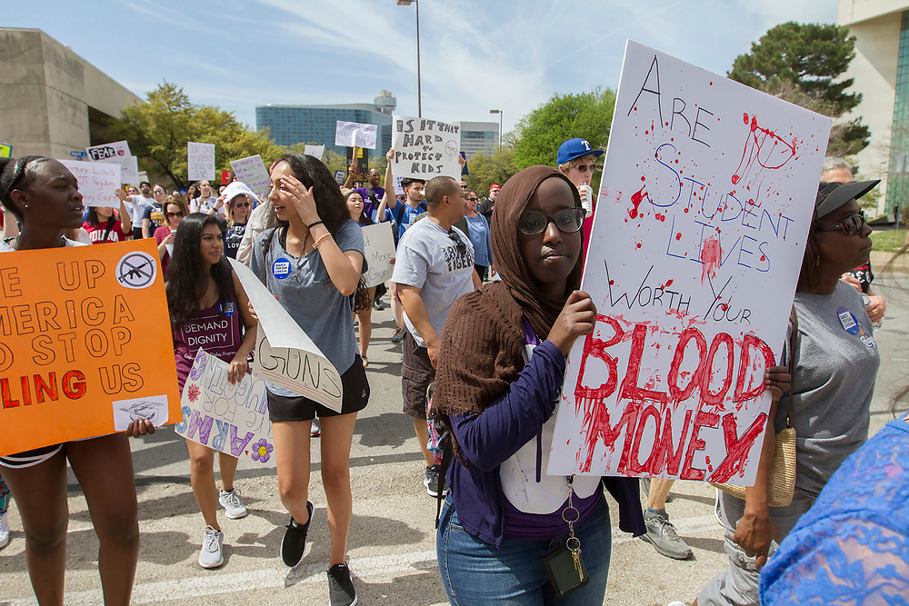 A student holds a dramatic sign to illustrate the lack of safety in schools during the latest spate of  shootings during the March for Our Lives event at Dallas City hall on Saturday.