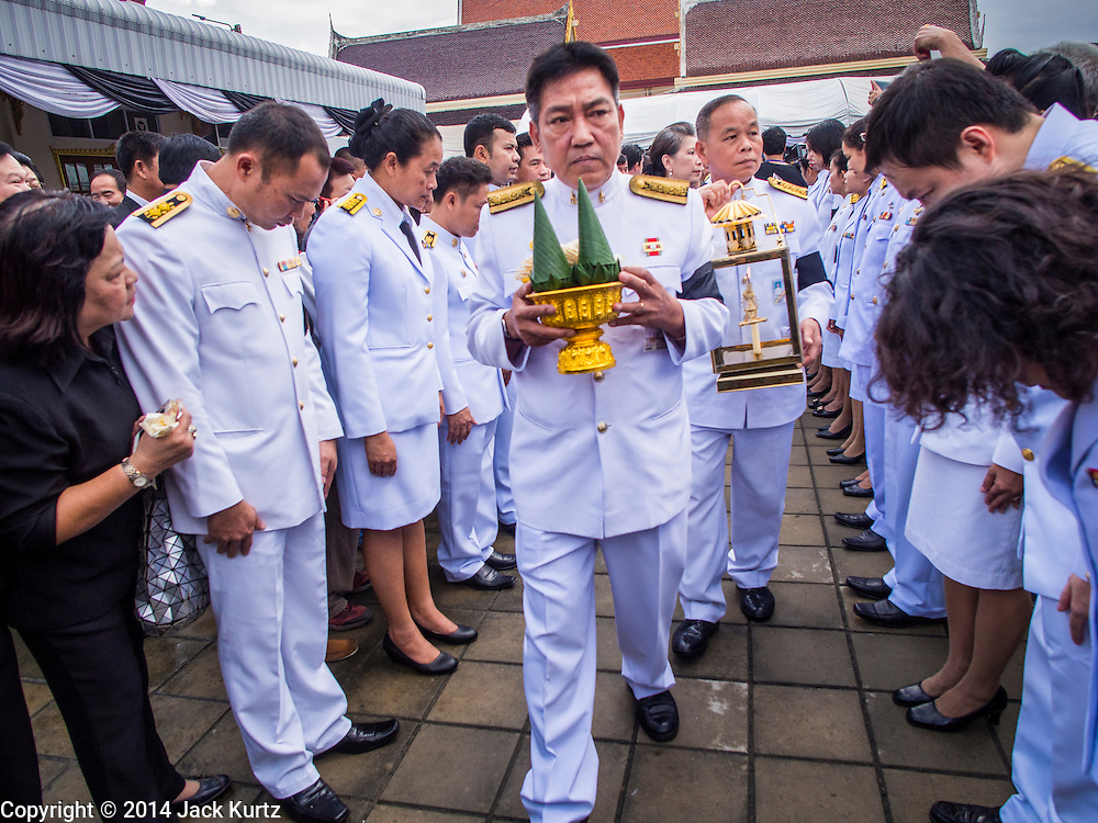 19 OCTOBER 2014 - BANG BUA THONG, NONTHABURI, THAILAND:  Representatives of the Palace carry in the flame used to light Apiwan Wiriyachai's cremation at Wat Bang Phai in Bang Bua Thong, a Bangkok suburb, Sunday. Apiwan was a prominent Red Shirt leader. He was member of the Pheu Thai Party of former Prime Minister Yingluck Shinawatra, and a member of the Thai parliament and served as Yingluck's Deputy Prime Minister. The military government that deposed the elected government in May, 2014, charged Apiwan with Lese Majeste for allegedly insulting the Thai Monarchy. Rather than face the charges, Apiwan fled Thailand to the Philippines. He died of a lung infection in the Philippines on Oct. 6. The military government gave his family permission to bring him back to Thailand for the funeral. His cremation was the largest Red Shirt gathering since the coup.    PHOTO BY JACK KURTZ