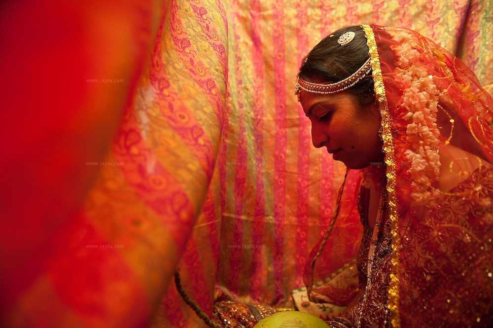 An Indian bride wearing a red saree sits behind a red veil, holding a coconut and waiting for the bridegroom to arrive, during an arranged  Hindu wedding in Andra Pradhesh, India, April 2009
