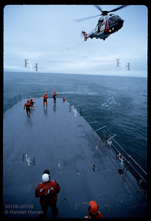Helicopter hovers above coast guard ship Tyr as crew practices transfer of items by cable. (v) Iceland