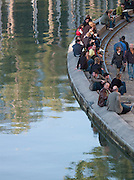 People sitting by the water at the Canal Saint Martin, Paris, France