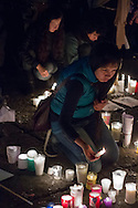 """A girl lights a candle in the """"Zocalo"""" plaza after a march in favor of the 43 missing students in Guerrero state."""
