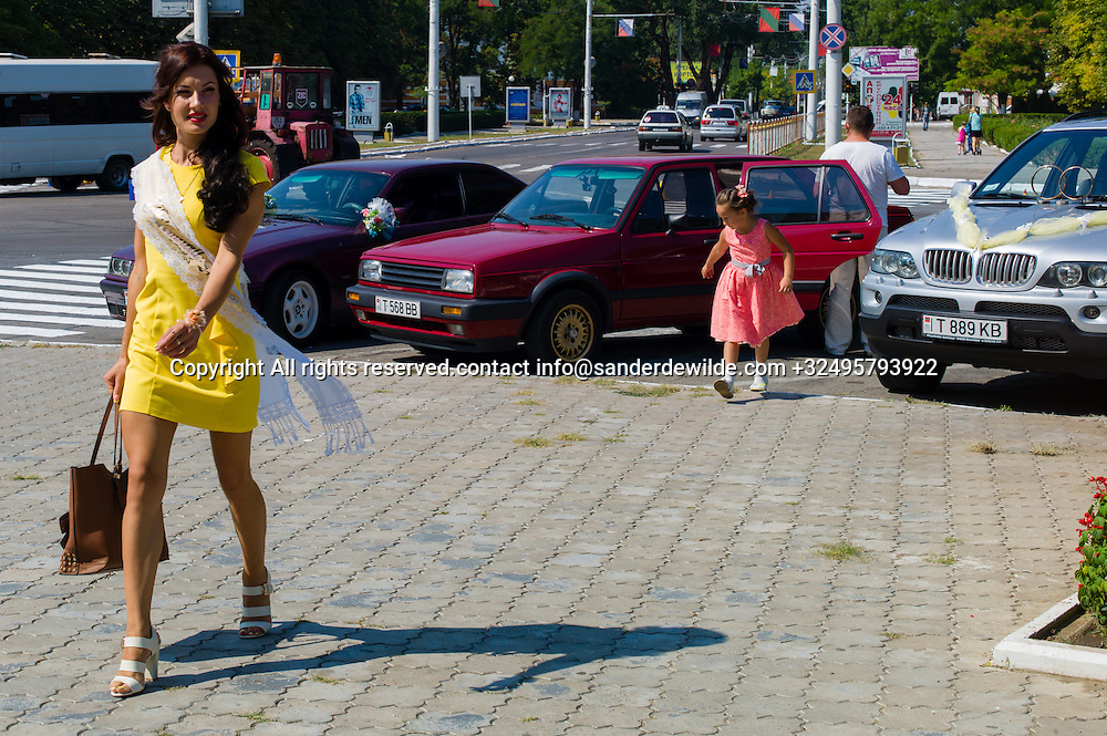 20150829  Moldova, Transnistria,Pridnestrovian Moldavian Republic (PMR) Tiraspol. This woman in yellow is not miss Tiraspol, she is dressed up for a wedding and witnesses wear a sash for the occassion.