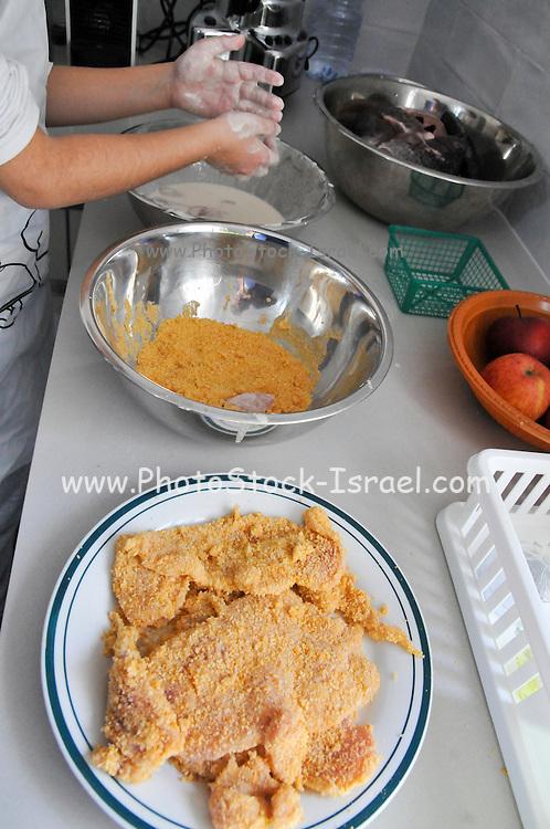Preparing schnitzel Fried breaded chicken breast. applying the coating